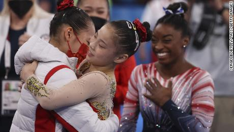 Chinese gymnasts  Tang Xijing and Guan Chenchen, and US gymnast Simone Biles celebrate after the women's balance beam final at the Tokyo Olympics on August 3.