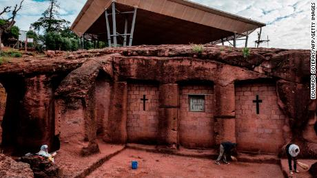 People stand next to the church of Saint Mercurius in Lalibela in 2019, which is covered by a shelter protecting its rock-hewn structure from erosion.