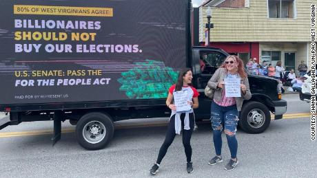 Organizers Shana Gallagher and Rylee Haught pose with a pro-For The People Act truck at the Grafton Memorial Day parade.