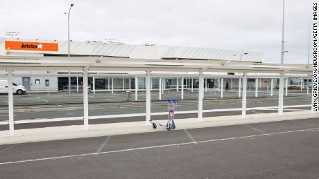 Un carrello per i bagagli abbandonato di fronte al terminal Jetstar del terminal nazionale dell'aeroporto di Auckland il 7 ottobre 2020, due giorni prima delle restrizioni dell'area di Auckland messe in atto dopo che il Covid-19 è riemerso nella comunità.