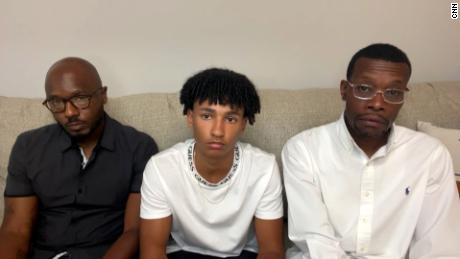 Roy Thorne, left, is seen with his 15-year-old son Samuel, in the middle, and real estate agent Eric Brown.  The three were handcuffed by officers in Wyoming, Michigan, as they visited a home.