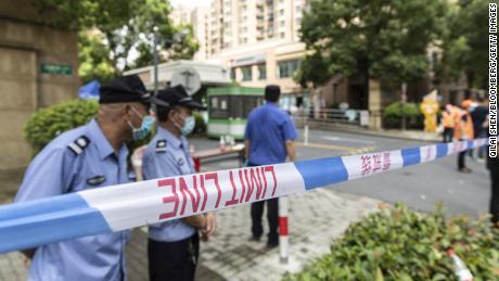 Polizia, guardie di sicurezza e volontari aiutano a isolare un quartiere che è stato bloccato dopo che un residente è risultato positivo al Covid-19, a Shanghai, in Cina, il 3 agosto 2021.