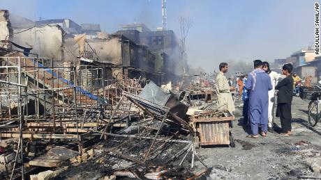 Afghans inspect stores damaged after fighting between the Taliban and Afghan security forces in the northern Afghan town of Kunduz on Sunday, August 8, 2021.