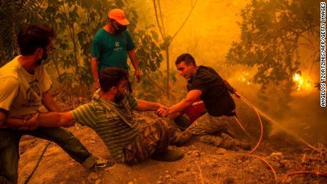 La gente del posto combatte gli incendi nel villaggio di Gouves a Evia, in Grecia.