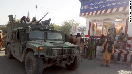 Taliban fighters stand guard at a checkpoint in Kunduz city, northern Afghanistan, on Monday.