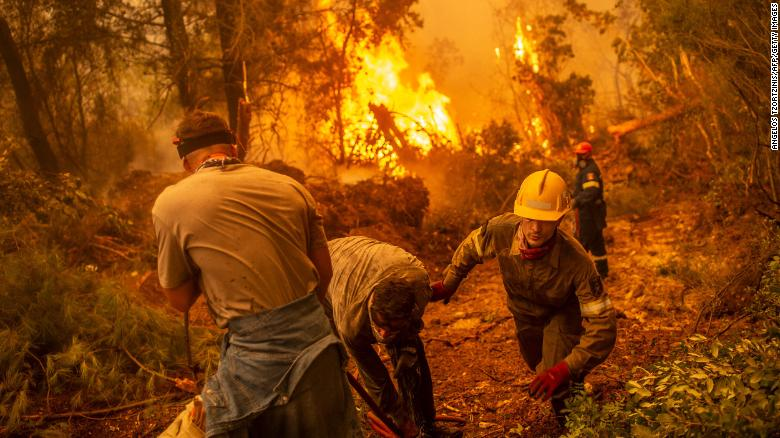 Firefighters and volunteers use a water hose near a burning blaze trying to extinguish a fire in the village of Glatsona on Evia island, on August 9.