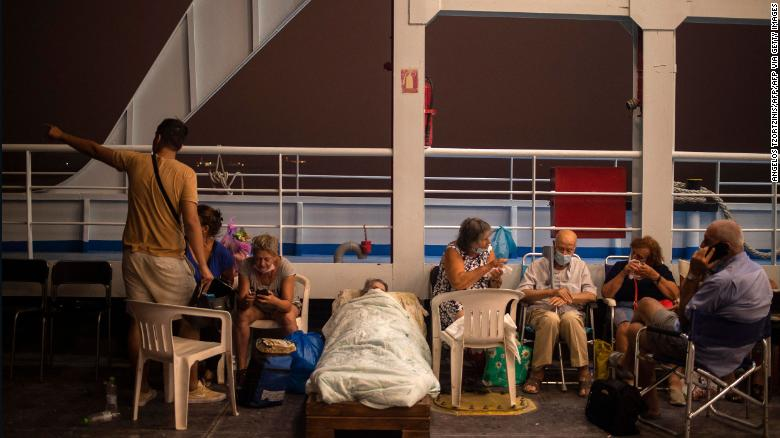 Elderly people are seen on chairs and makeshift bed onboard a ferry at the port of the village of Pefki, during a wildfire at Pefki village on Evia.