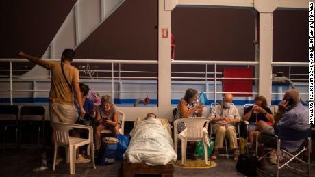 Ηλικιωμένοι σε καρέκλες και πρόχειρα κρεβάτια εθεάθησαν στο σκάφος κατά τη διάρκεια πυρκαγιάς στο χωριό Μπέφκι της Εύβοιας, στο λιμάνι της Πεύκης.
