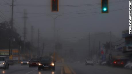 تسير المركبات خلال هطول أمطار غزيرة في فيجا ألتا ، بورتوريكو ، 10 أغسطس 2021 ، قبل العاصفة الاستوائية فريد.