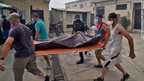 Des médecins emportent le corps d'un homme lors d'un incendie de forêt le 10 août à DC Oso, l'une des villes les plus peuplées de la région de Kabili en Algérie.