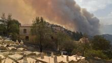 Smoke billows from a wildfire in the forested hills of the Kabylie region, east of the capital Algiers, on August 10, 2021. - Wildfires fanned by blistering temperatures and tinder-dry conditions have killed at least seven people in Algeria, the interior minister said, adding the fires had criminal origins.