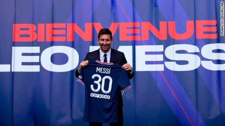 Messi holds his jersey after a press conference.