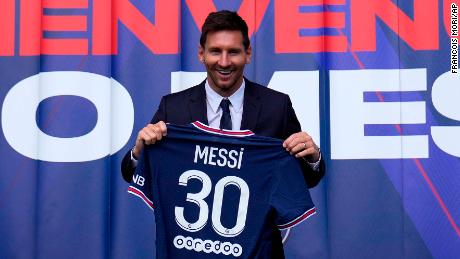"""Lionel Messi holds his jersey after a press conference Wednesday, Aug. 11, 2021 at the Parc des Princes stadium in Paris. Lionel Messi said he's been enjoying his time in Paris """"since the first minute"""" after he signed his Paris Saint-Germain contract on Tuesday night. The 34-year-old Argentina star signed a two-year deal with the option for a third season after leaving Barcelona. (AP Photo/Francois Mori)"""