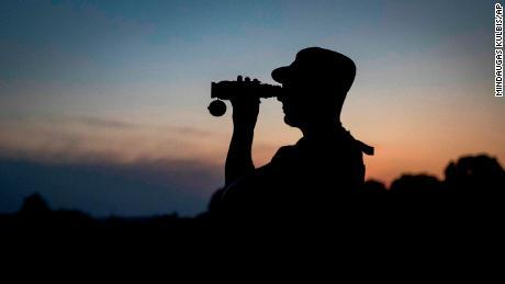 Un membre du Service des gardes-frontières de l'État lituanien regarde à travers des jumelles alors qu'il patrouille à la frontière avec la Biélorussie, près du village de Purvenai, en Lituanie.