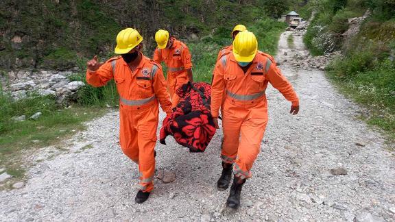 جنود يحملون جثة ضحية من موقع انهيار أرضي في هيماشال براديش ، الهند ، في 11 أغسطس.