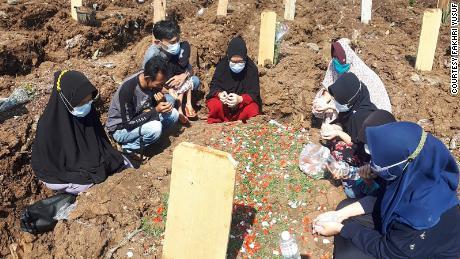 A família de Warsa Tirta se reúne ao redor de seu túmulo em Jacarta, Indonésia.