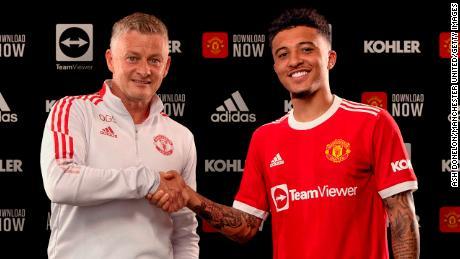 Jadon Sancho le da la mano al técnico del Manchester United, Ole Gunnar Solskjaer, tras firmar con el club.