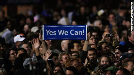 """An Obama supporter holds up a sign reading """"Yes we can"""" as  President-elect Barack Obama gives his election night victory speech on November 4, 2008, in Chicago's Grant Park."""