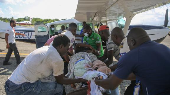 An injured woman is transferred to a plane to be flown to Port-au-Prince, Haiti, on August 14.