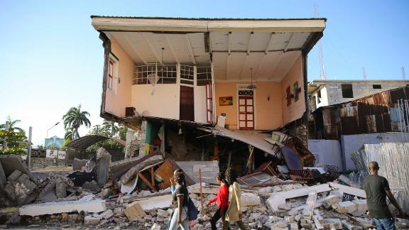 People walk past a Les Cayes home on August 14.