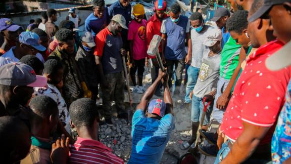 A man uses a sledgehammer in an attempt to rescue people from the remains of a home in Les Cayes on August 14.