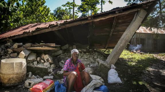 A woman sits in front of a destroyed house in Les Cayes on August 15.