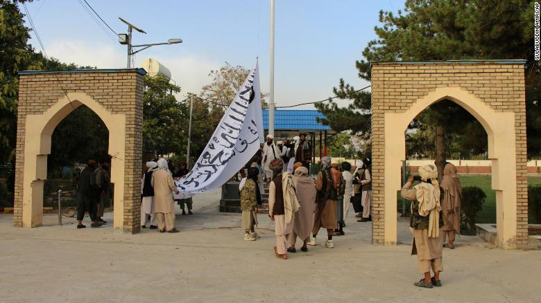 Taliban fighters raise their flag at the provincial governor's house in Ghazni, southeastern Afghanistan, on August 15, 2021.