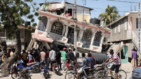 Residents survey a damaged building following a 7.2-magnitude earthquake in Les Cayes, Haiti, on Sunday, Aug. 15, 2021. The U.S. deployed search and rescue teams to help find survivors among the debris of collapsed buildings in Haiti as the death toll soars from Saturdays massive earthquake. Photographer: Jonathan Alpeyrie/Bloomberg via Getty Images