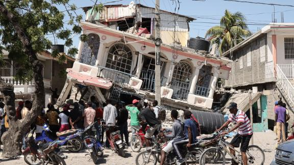 Residents of Les Cayes, Haiti, survey a damaged structure on August 15, a day after the 7.2 magnitude earthquake struck the country.