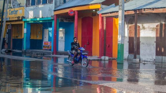 A man rides through water-logged streets in Les Cayes on August 15.