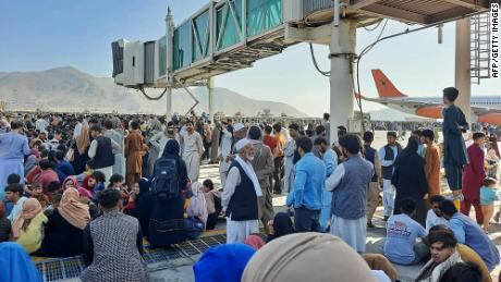 Afghans crowd the tarmac of Kabul's international airport on Monday.