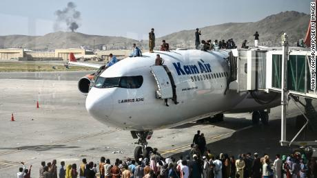Afghan people climb atop a plane attempt to leave Kabul on Monday. The US has come under scrutiny over its hasty and chaotic withdrawal, which continued at the airport on Tuesday.