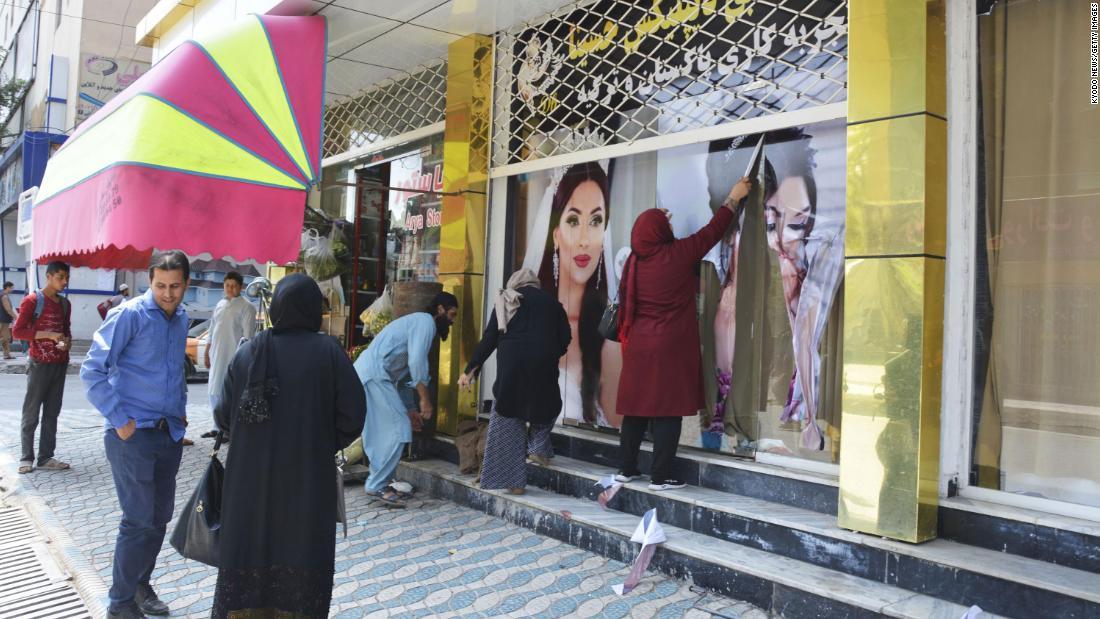 Los trabajadores de un salón de belleza quitan fotografías grandes de mujeres de la pared en Kabul el 15 de agosto de 2021.