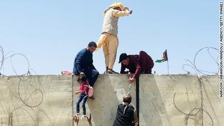 Afghans climb a wall around the Hamid Karzai International Airport during the rush to escape Kabul on Monday.