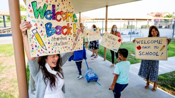 Third-grade teacher Candace Ropp, left, welcomes students back for the first day of class Monday at Stanford Elementary School in Garden Grove, California.