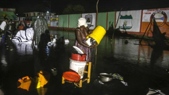 A woman recovers her belongings at a flooded refugee camp. Emergency officials are bracing for heavy rains and floods as Tropical Depression Grace is on track to hit Haiti.
