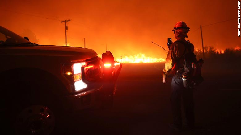 Firefighters monitor the Dixie Fire as it burns along Highway 395 on near Janesville, California.