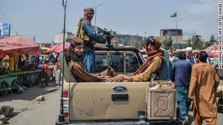Taliban fighters on a pick-up truck move around a market in Kabul on Tuesday.