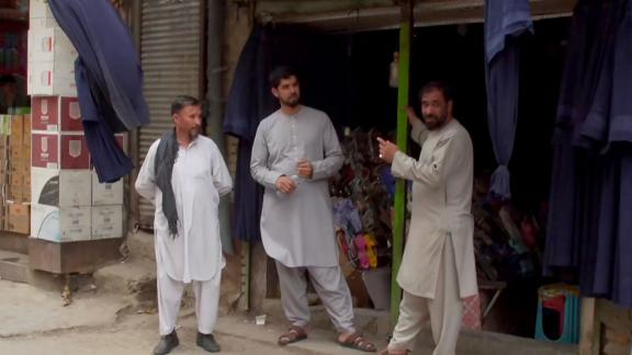 Men stand outside a clothing store in central Kabul. The store's owner told CNN he has been selling many more burqas in recent days.