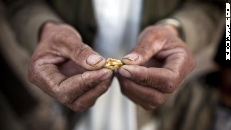 An Afghan man holds a small piece of gold, prospected from the site of a proposed Qara Zaghan mine in 2011.