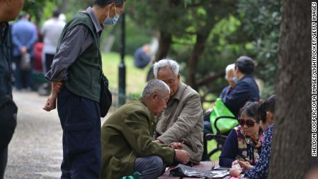 Senior citizens sit together while playing cards in Fuyang, China's Anhui province, on May 12.