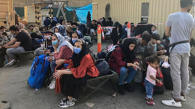 People wait to be evacuated from Afghanistan at the airport in Kabul on August 18, 2021 following the Taliban stunning takeover of the country.