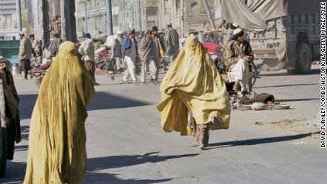 Two Afghan women, wearing yellow niqabs, walk in Kandahar, Afghanistan, 1996.