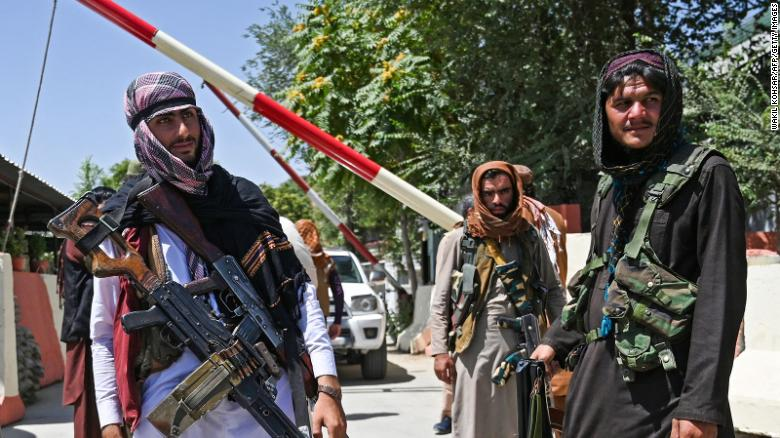 Taliban fighters stand guard along a roadside near the Zanbaq Square in Kabul on August 16, 2021.