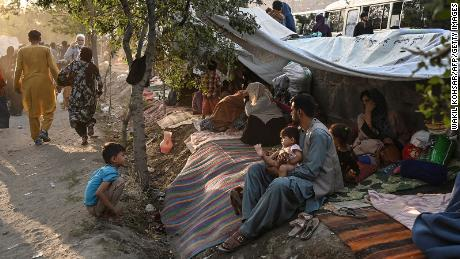 Displaced Afghan families, who fled from Kunduz, Takhar and Baghlan province due to battles between Taliban and Afghan security forces, sit in front of their temporary tents in Kabul on August 11, 2021.
