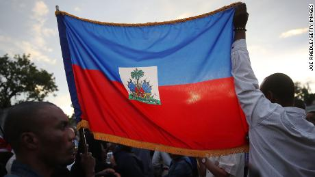 MIAMI, FL - JANUARY 12: (EDITORS NOTE: Caption contains profanity.)  People hold a Haitian flag as they gather together to mark the 8th anniversary of the massive earthquake in Haiti and to condemn President Donald Trump's reported statement about immigrants from Haiti, Africa and El Salvador on January 12, 2018 in Miami, Florida. President Trump is reported to have called those places 'shithole countries' whose inhabitants are not desirable for U.S. immigration.  (Photo by Joe Raedle/Getty Images)