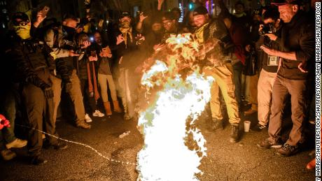 A Proud Boy adds fuel to a Black Lives Matter flag on fire as leader Enrique Tarrio and other members gather in the streets following the 'Million MAGA March' on December 12.