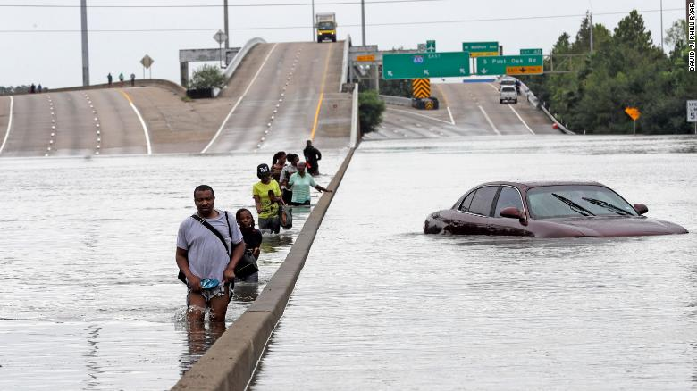 Evacuees wade down a submerged section of Interstate 610 in Houston after Hurricane Harvey in 2017 caused widespread flooding.