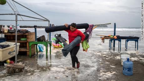 Una mujer toma sombrillas de la playa cuando las fuertes olas golpearon la costa debido al huracán Grace en Boca del Río, Veracruz, México, el 20 de agosto de 2021.