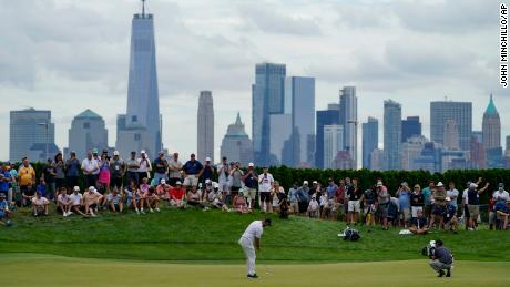 Jon Rahm, of Spain, putts on the 18th green as the Manhattan skyline looms in the distance.